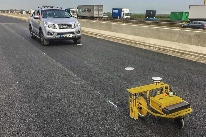 Robotic pre-marker marking temporary lines on new concrete during highways construction project